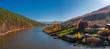 Leinwandbild Motiv Aerial view; drone flying around little village on riverside; old buildings in autumn landscape, colorful forest; orange yellow foliage of birch trees; beautiful countryside near pond, Porogi, Ural