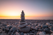 Stone Pyramid On The Background Of Sunset And Sea On Pebble Beach Symbolizing Stability, Zen, Harmony And Balance
