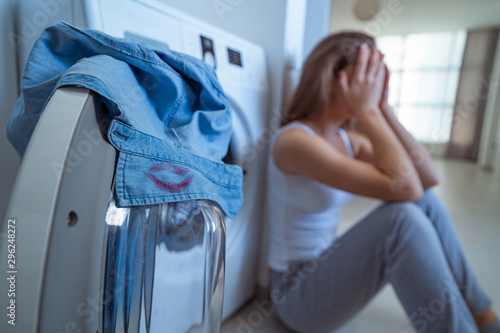 Photo Surprised upset stressed crying woman found on the collar of her husband's shirt female red lipstick marks while laundry