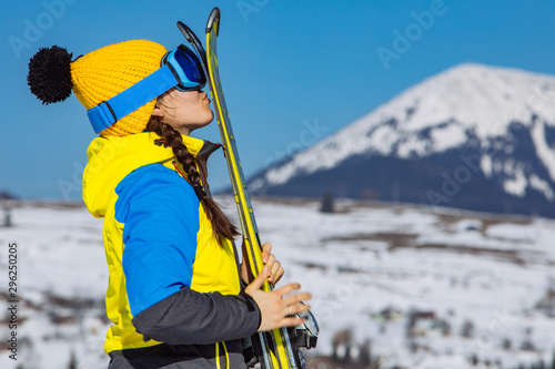 Fotomural  young smiling pretty woman holding ski. mountains on background