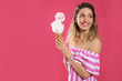 Leinwandbild Motiv Portrait of young woman holding cotton candy dessert on pink background, space for text