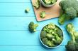 Leinwandbild Motiv Flat lay composition of fresh green broccoli on blue wooden table, space for text