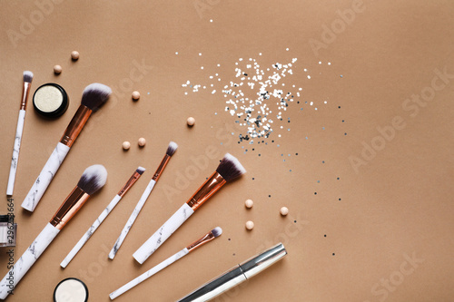 Flat lay composition with makeup brushes on brown background Canvas Print