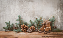 Christmas Tree Branches With Cones On A Dark Wooden Board Against A Gray Concrete Wall.