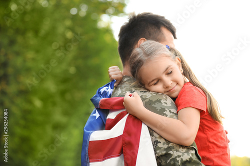 Obraz Father in military uniform with American flag hugging his little daughter at green park - fototapety do salonu
