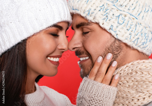 Foto auf AluDibond Logo Lovely young couple in knitted hats on red background, closeup. Christmas celebration