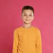 Cute little boy posing on pink background