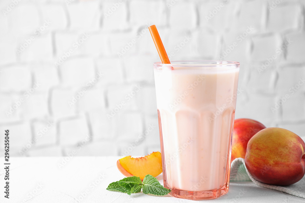 Fototapeta Tasty peach milk shake in glass and fresh fruit on white table. Space for text
