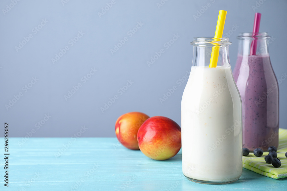Fototapeta Tasty peach and blueberry milk shakes in bottles on light blue wooden table. Space for text