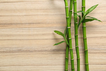 Green Bamboo Stems And Space For Text On Wooden Background, Top View