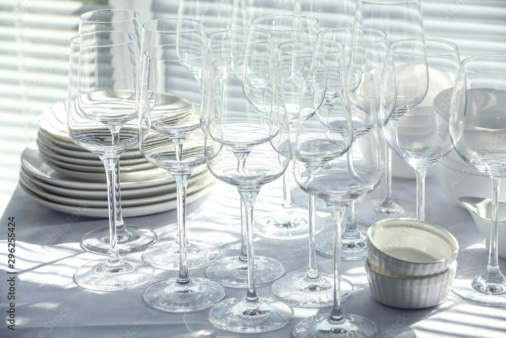 Fototapeta Set of empty wine glasses and dishware on table indoors