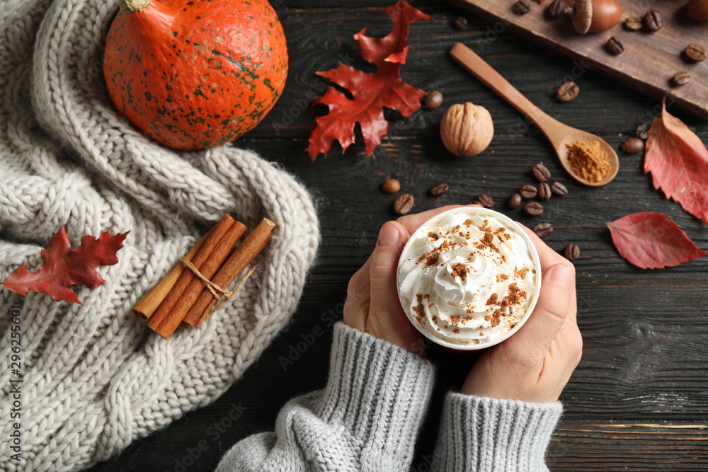 Fototapeta Woman holding cup with tasty pumpkin spice latte at black wooden table, top view