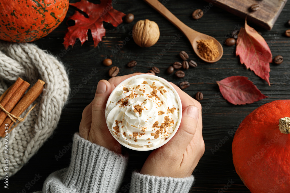 Fototapeta Woman holding cup with tasty pumpkin spice latte at black wooden table, closeup