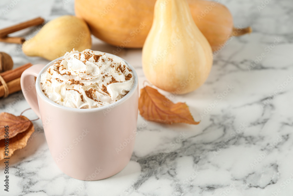 Fototapeta Cup with tasty pumpkin spice latte on white marble table. Space for text