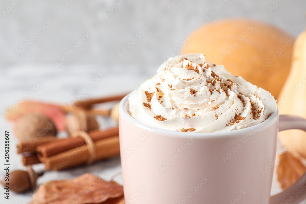 Fototapeta Cup with tasty pumpkin spice latte on white table, closeup