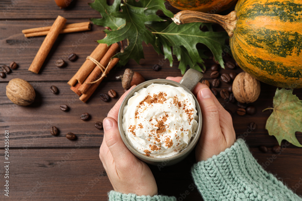 Fototapeta Woman with cup of tasty pumpkin spice latte at wooden table, top view