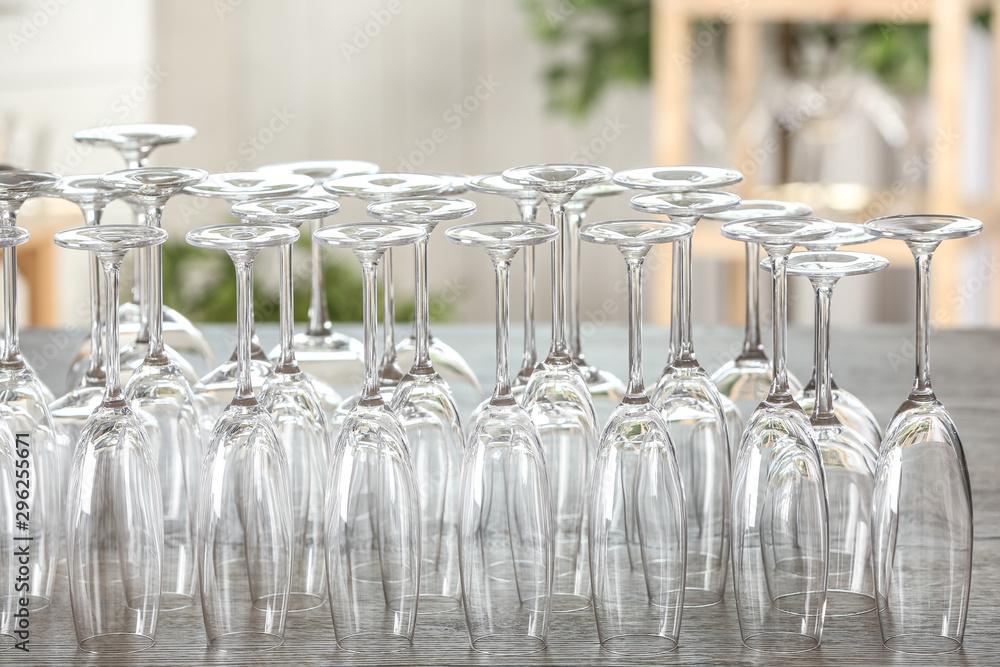 Fototapeta Empty glasses on wooden table against blurred background