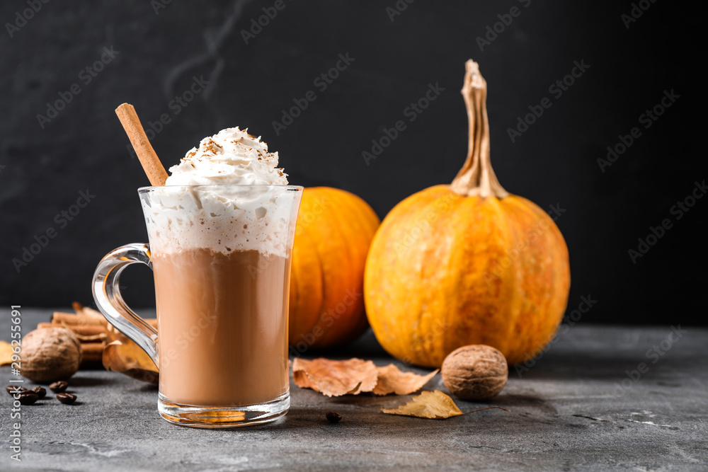Fototapeta Pumpkin spice latte with whipped cream and cinnamon stick in glass cup on grey table