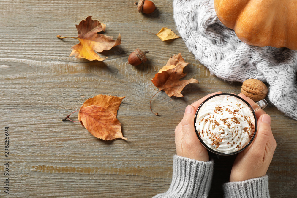 Fototapeta Woman with cup of pumpkin spice latte at wooden table, top view