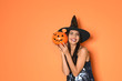 Leinwandbild Motiv Beautiful woman wearing witch costume with Jack O'Lantern candy container for Halloween party on yellow background, space for text