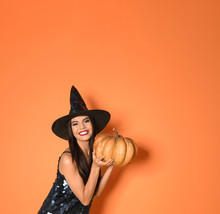 Beautiful Woman Wearing Witch Costume With Pumpkin For Halloween Party On Yellow Background, Space For Text