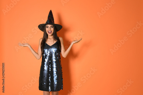 Excited woman wearing witch costume for Halloween party on yellow background, space for text