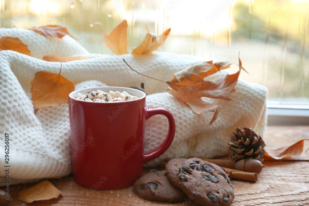 Fototapeta Composition with cup of hot drink, sweater and autumn leaves on windowsill. Cozy atmosphere