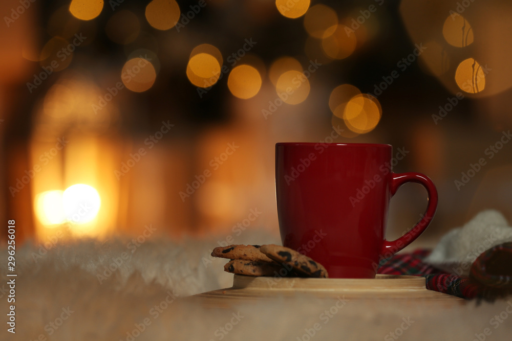 Fototapeta Cup of drink on white fur against blurred lights, space for text. Cozy winter