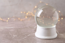 Snow Globe On Marble Table Against Festive Lights, Space For Text. Christmas Season