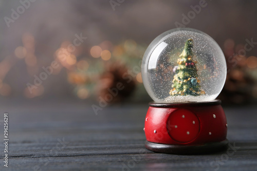 Foto auf Gartenposter Baume Snow globe with Christmas tree on grey wooden table against festive lights, space for text