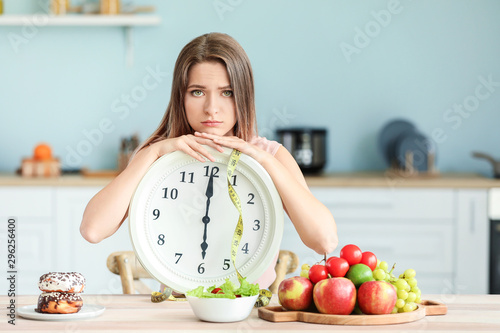 Fotografiet  Sad woman with clock and food sitting in kitchen. Diet concept