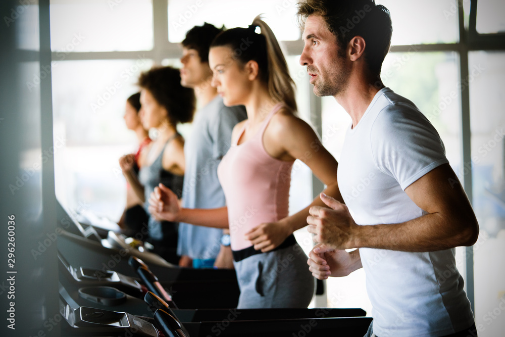 Fototapety, obrazy: Fit people running in machine treadmill at fitness gym