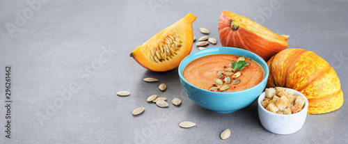 Pumpkin cream soup with croutons and seeds over gray texture.