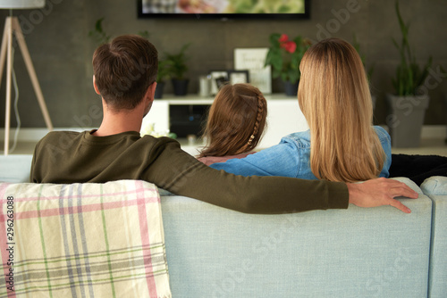 Rear view of family with one child watching tv Wallpaper Mural