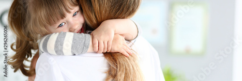 Fotografiet  Portrait of cheerful girl child in modern office of professional physician hugging caring pediatrician woman with great joy