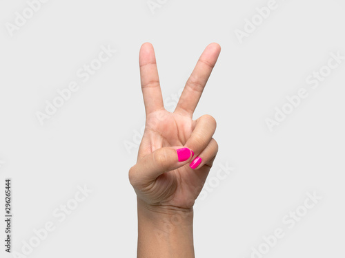 Valokuva  Close-up of a woman's hand showing V sign with a pink nail polish isolated on a white background