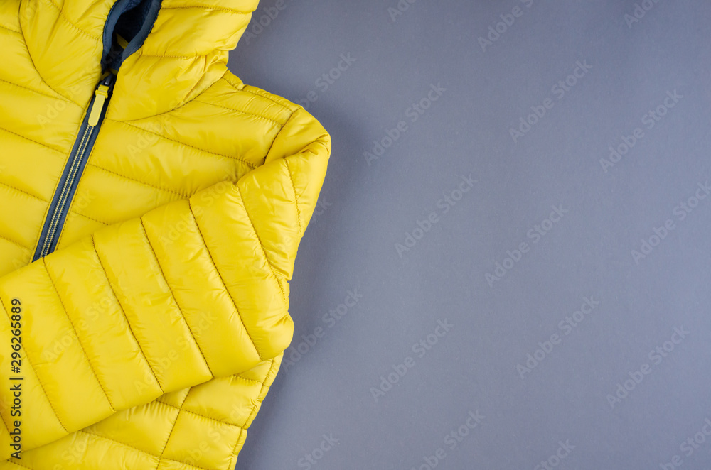 Fototapety, obrazy: Yellow kids winter jacket composition on yellow background.