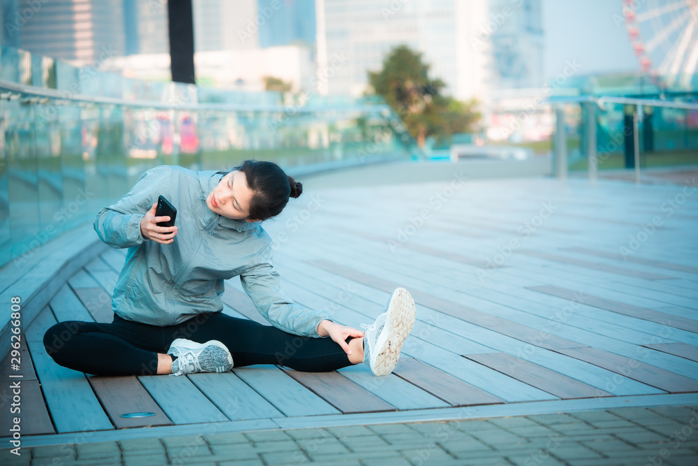 Fototapety, obrazy: Woman doing warm up and watch on her smartphone