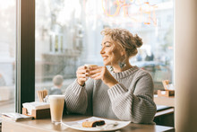 Woman Drinking Coffe By The Wi...