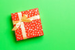 canvas print picture - Gift box with gold bow for Christmas or New Year day on green background, top view with copy space