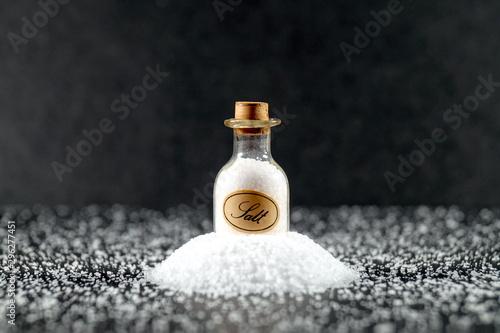 Photo old vintage Salt Miniature glass and Crystals of salt on a dark table