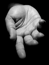 Black And White Photo Of A Mans Hand With Fingers Slightly Apart Asking For Help In Low Key Lighting