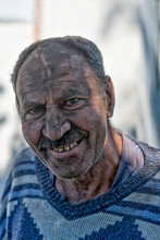 Elderly Smiling Man With A Face In Black Dust