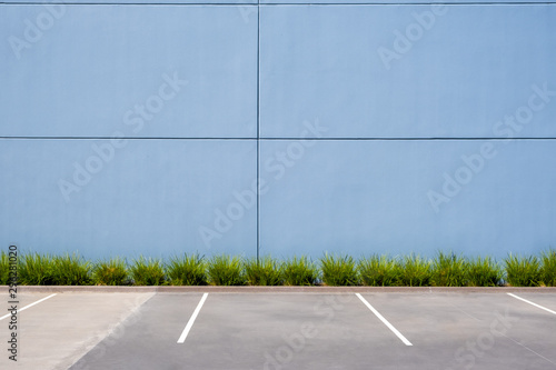 Fotografía  Empty parking spaces against clean concrete wall of an industrial building with