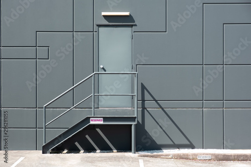 Rear entrance door with metal stairs into industrial building - minimal clean ge Canvas Print