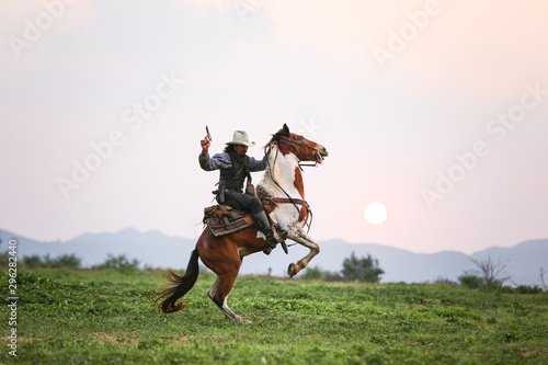 Mon riding horse against sunset with holding gun Tablou Canvas