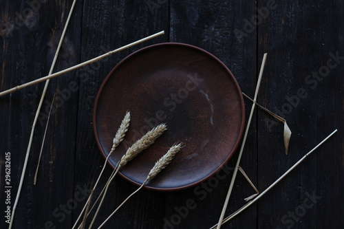 Fotografie, Tablou  three wheat spikelets on a clay plate on a black burnt