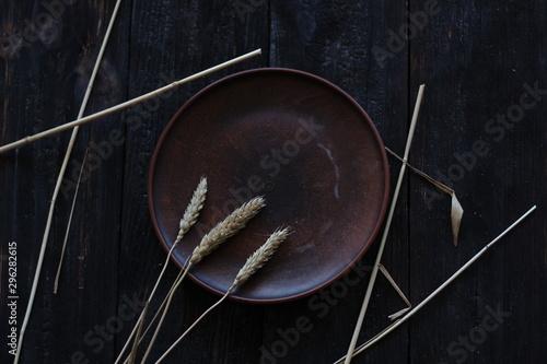 Fényképezés  three wheat spikelets on a clay plate on a black burnt