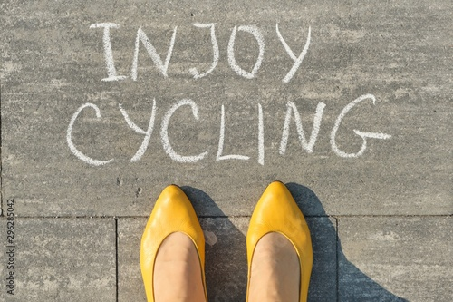 Enjoy cycling, text on gray sidewalk with woman legs, top view