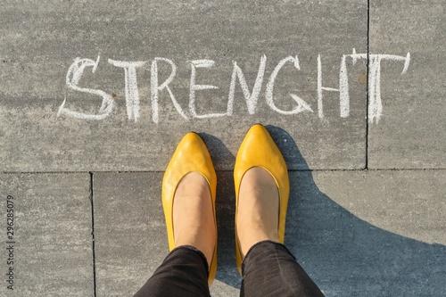 Fototapeta  Strength, written on gray sidewalk with woman legs, top view